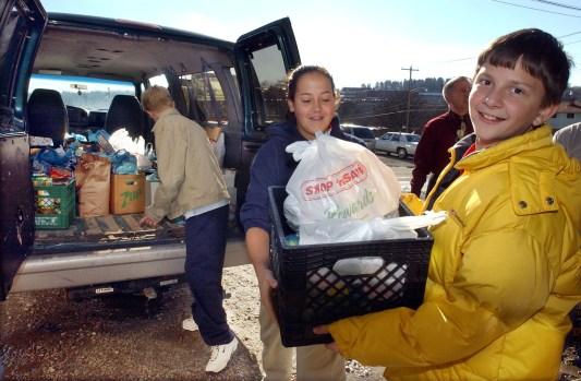 Central Christian Academy students form a chain to unload supplies for an Operation Drumstick Thanksgiving food collection at Washington City Mission in 2003. (Robert J. Pavuchak/Post-Gazette)