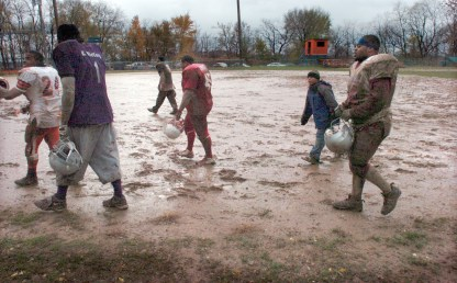 Players walk off of the muddy football field behind the Fort Pitt Elementary School in Garfield at the end of the 2007 Turkey Bowl, a neighborhood football game played every Thanksgiving. (Darrell Sapp/Post-Gazette)
