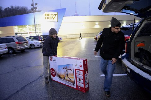 Nate Murano and Kent Diasabeygunawardena of the North Side load up a 55-inch TV from Best Buy in Ross on Black Friday 2014. (Rebecca Droke/Post-Gazette)