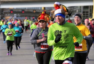 Andrea Vargo, West Mifflin, left, and D.J. Kracinovsky, right, get close to the finish line of the 2014 YMCA Turkey Trot. (John Heller/Post-Gazette)