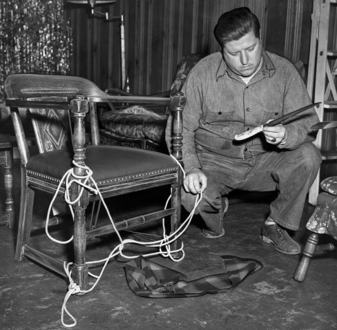 Special Patrolman Alec Haberman examines chair in which robbery victim Rose Palermo, 60, was tied during the crime. (Post-Gazette Archive)