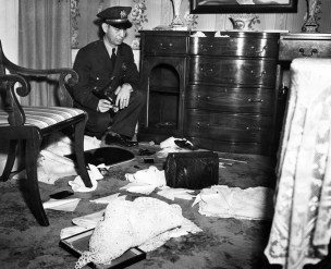 Green Tree police chief W.J. Reed inspects the buffet drawer ransacked by thieves. (Post-Gazette Archive)