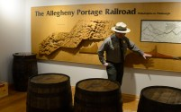 Ranger Doug Bosley uses a display while talking about the elevation and how 10 engine houses were used to get cargo over the Allegheny Mountains, in the Portage Museum. In the forground are some of barrels that would have been used to ship. (Darrell Sapp/Post-Gazette)