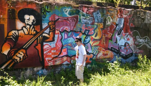 Shane Pilster, graffiti artist, graphic designer, and urban arts coordinator for the Rivers of Steel National Heritage Area, in front of a graffiti mural at the Carrie Furnace site. (Lake Fong/Pittsburgh Post-Gazette)