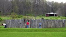 Visitors look at the stockade at Fort Necessity. In the background is the visitor's center.
