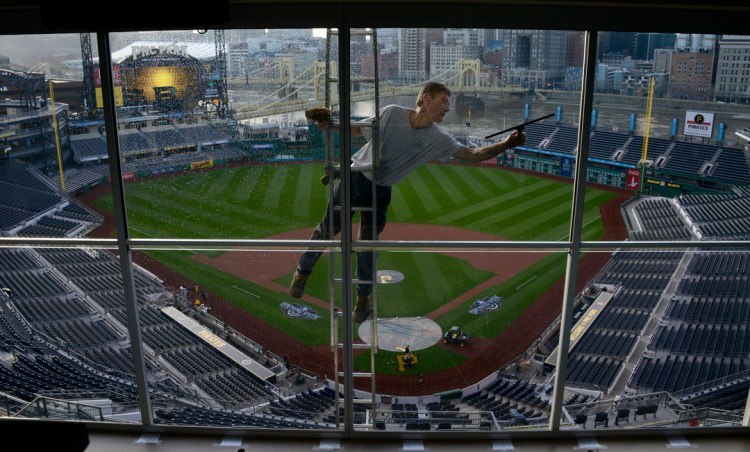 Frank Giordano of Carrick stretches to use his squeegee on the windows of the press box overlooking the field at PNCPark hours before the Pirates' opening day game. (Darrell Sapp/Post-Gazette)