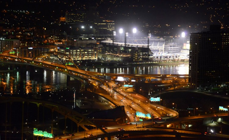 The bright lights , at PNC Park , outshine the commuter traffic crossing Point State Park with the Ft. Pitt and Ft Duquesne Bridges, early Monday morning.  The lights were on  for Pirates Home Opener. (Darrell Sapp/Post-Gazette)