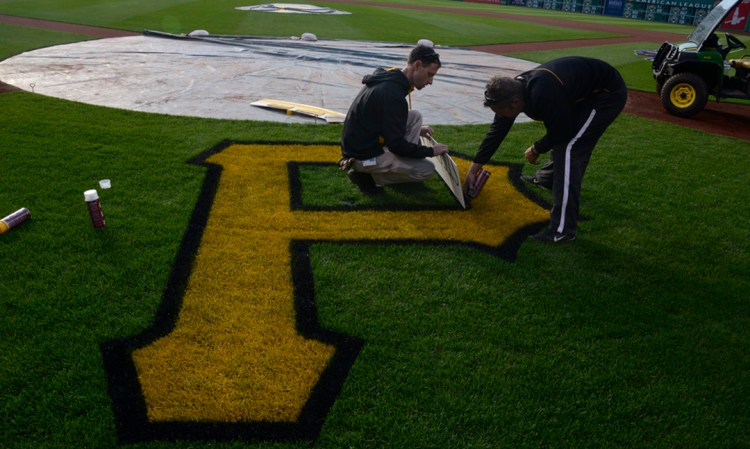 """Andrew Burnette holds the line as Derek Hurlburt  paints the black edge to the Pirates' logo """"P"""" , behind home plate at PNC Park for the Pirates home opener. (Darrell Sapp/Post-Gazette)"""