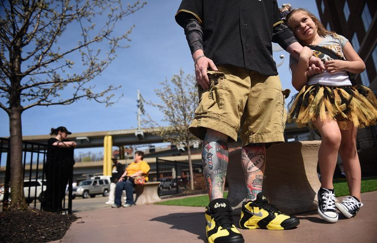 Ken Brisco of Whitehall shows off his Pittsburgh tattoos while daughter Natalya, 4, holds his hand. (Steve Mellon/Post-Gazette)