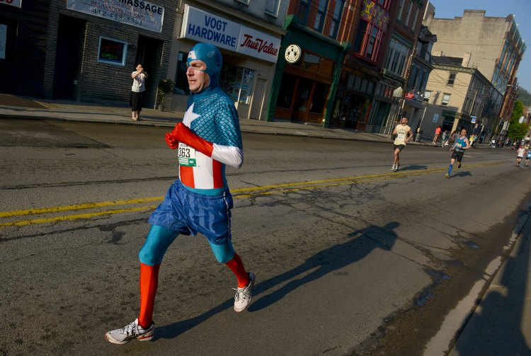 A marathon participant dressed as Captain America runs on Carson Street in the South Side during the 2015 Pittsburgh Marathon, on Sunday, May 3, 2015. (Michael Henninger/Post-Gazette)