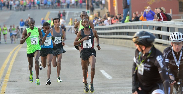 Elite runners leave the Strip District and head over the 16th Street Bridge.  (Larry Roberts/Post-Gazette)