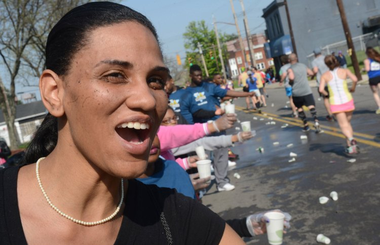 Volunteer Erica Motley cheers and hands water to runners as they make their way down Frankstown Avenue in Homewood. (Nate Guidry/Post-Gazette)