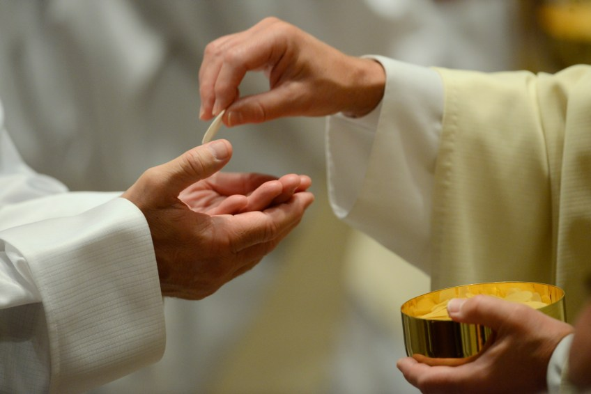 A priest passes out communion to a deacon during a Mass celebrated by Pope Francis at the Cathedral Basilica of Saints Peter and Paul in Philadelphia on Saturday.
