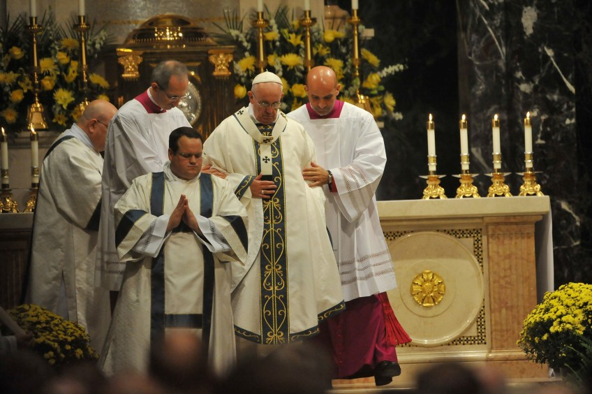Pope Francis gets helps getting down from the altar as he celebrates Mass with clergy, religious sisters and lay leaders at the Cathedral Basilica of Saints Peter and Paul in Philadelphia on Saturday.