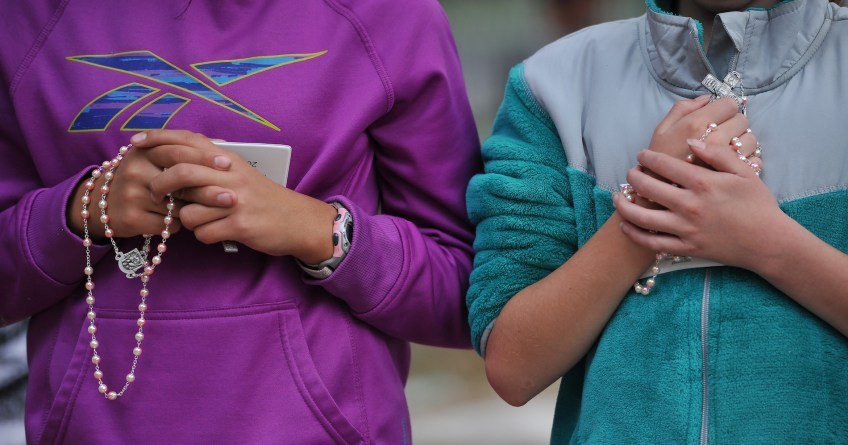 """Christina Farrell, 11, left, and Kelly Besyna, 11, kneel on the concrete sidewalk as they listen to Mass celebrated by Pope Francis along the Benjamin Franklin Parkway Sunday, September 27, 2015. Kelly Besyna said """" I feel so much closer to go God when I am holding the Rosary,"""" and Christina agreed. The girls drove  12-hrs. with the Farrell family to attend the Mass."""