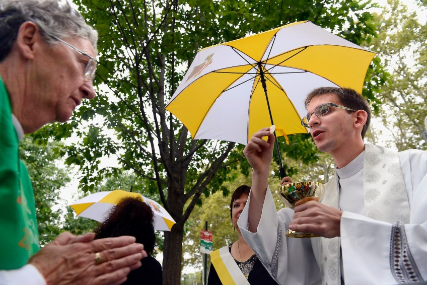 Father Andy LaFramboise of Saginaw, Mi., gives communion during the open air Mass celebrated by Pope Francis along the Benjamin Franklin Parkway in Philadelphia on Sunday, Sept. 27. (Rebecca Droke/Post-Gazette)