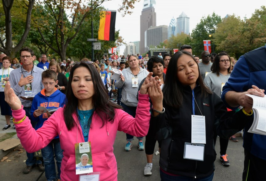 People pray as Pope Francis concludes his six -day trip to the United States with an open air Mass along the Benjamin Franklin Parkway in Philadelphia on Sunday, Sept. 27. (Rebecca Droke/Post-Gazette)
