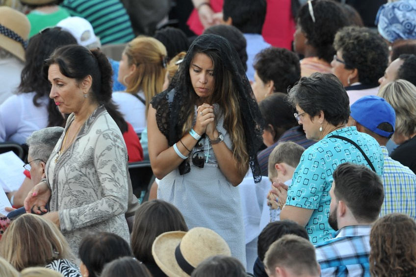 After receiving communion, a woman returns to her seat during the canonization Mass for Junipero Serra at the Basilica of the National Shrine of the Immaculate Conception on Wednesday.