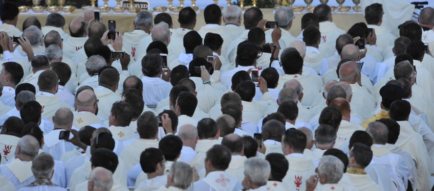 Priests pull out their phones as Pope Francis gives his homily during the canonization Mass for Junipero Serra at the Basilica of the National Shrine of the Immaculate Conception Wednesday.