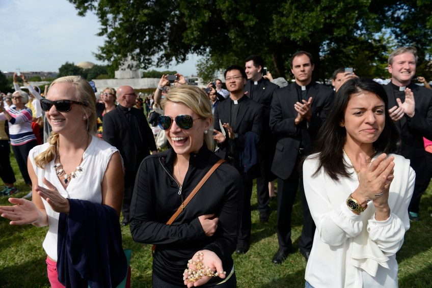 From left: Stephanie Laurine, Courtney Rosellini and Charlotte Pineda react as Pope Francis comes out onto the balcony of the U.S Capitol to greet the thousands of people gathered on the lawn to hear his address to Congress on Thursday.