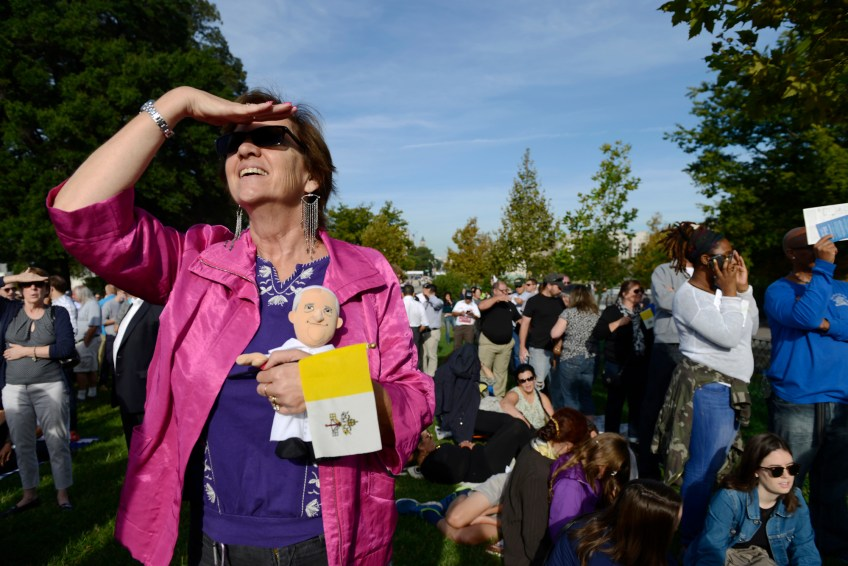 Jill Sullivan shields her eyes as she tries to see Pope Francis on the Jumbotrons set-up above the West Front Lawn for Pope Francis' address to a joint session of Congress in Washington, D.C. on Thursday.