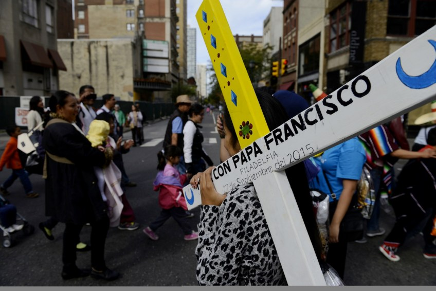 Sinai Flores of Kansas City, Mo., carries the cross of her diocese to get it blessed by Pope Francis during the public mass along the Benjamin Franklin Parkway in Philadelphia on Sunday, Sept. 27. (Rebecca Droke/Post-Gazette)