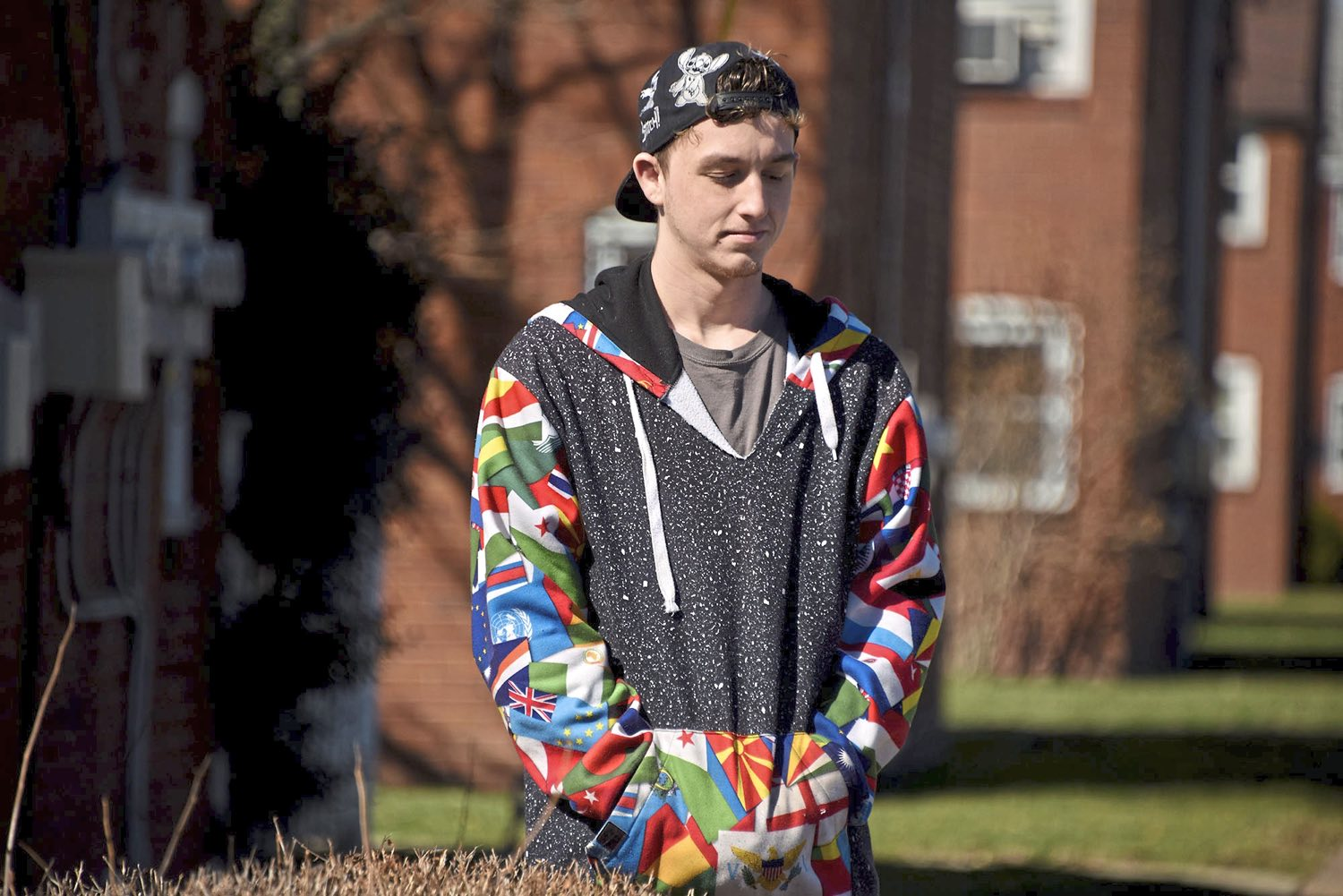 Carlynton class of 2017 graduate Patrick Zekler, of Neville Island, pauses as he talks about his uncle's overdose death while wearing his uncle's colorful hoodie, decorated with a pattern of flags, Monday March 5, 2018, in Neville Island. (Darrell Sapp/Post-Gazette)