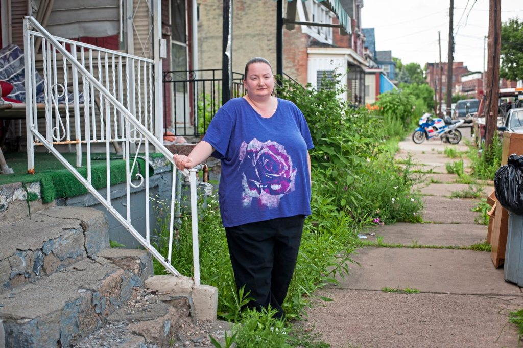 Jackie Stock, 33, outside her home in Hazelwood. Ms. Stock, a housekeeper at UPMC Mercy, is concerned she will be displaced from Hazelwood if her rent increases. (Stephanie Strasburg/Post-Gazette)