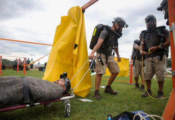 Andrew Nugent, left, of Burnsville, Ohio, a coal miner at the Consol Energy Harvey mine, is pulled by Rocky Roberts, center, of Moundsville, during a team mine rescue simulation at the Pennsylvania State Mine Rescue Contest Aug. 21. (Jessie Wardarski/Post-Gazette)