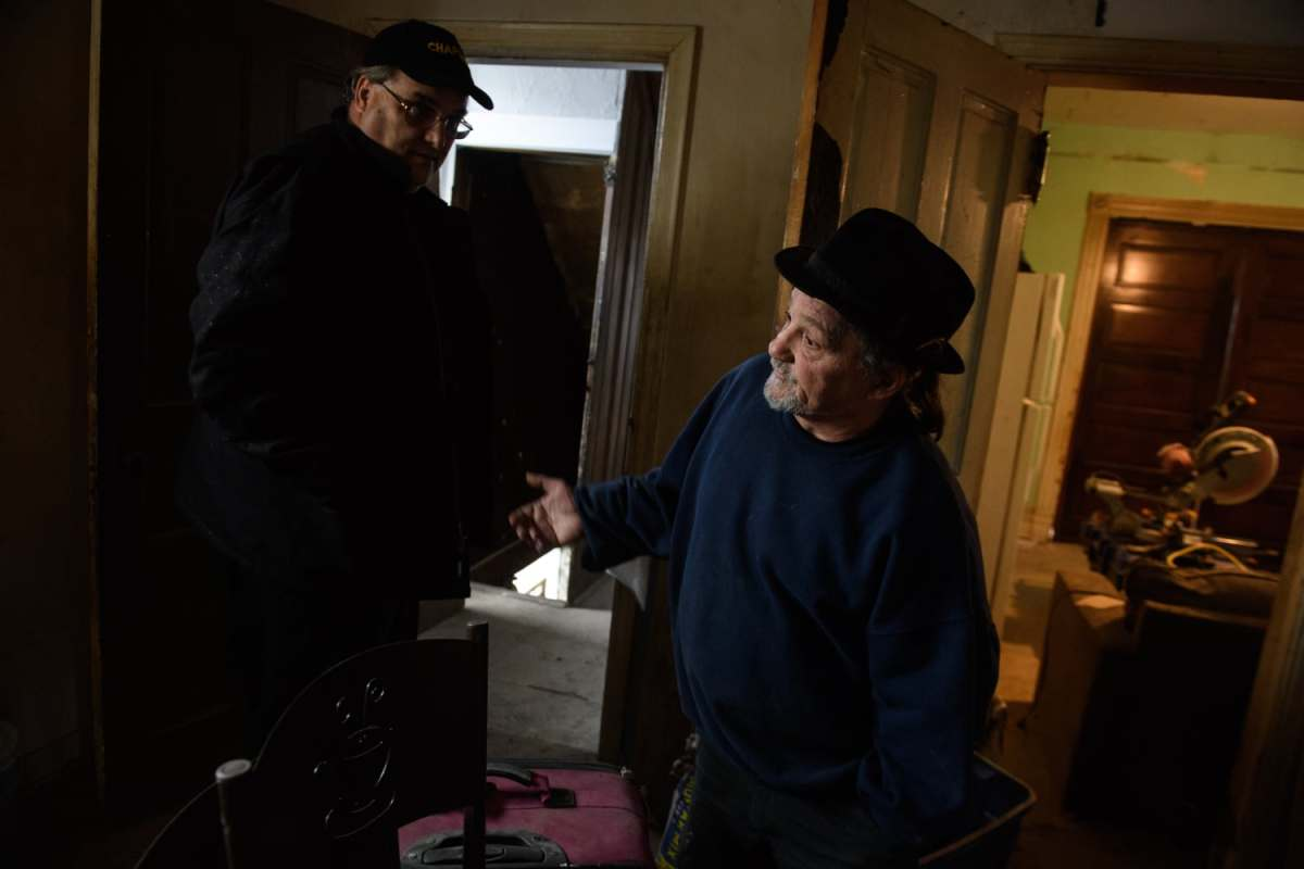 """Chaplain of the ARK Allegheny Recovery Krew Rev. Jay Geisler of St. Peter's Episcopal Church in Brentwood, left, and ARK recovery director Gus DiRenna talk in a former drug house on Thursday, Nov. 15, 2018, in Carrick. Both men are in recovery and are helping others through the creation of this and other """"Serenity Houses."""""""
