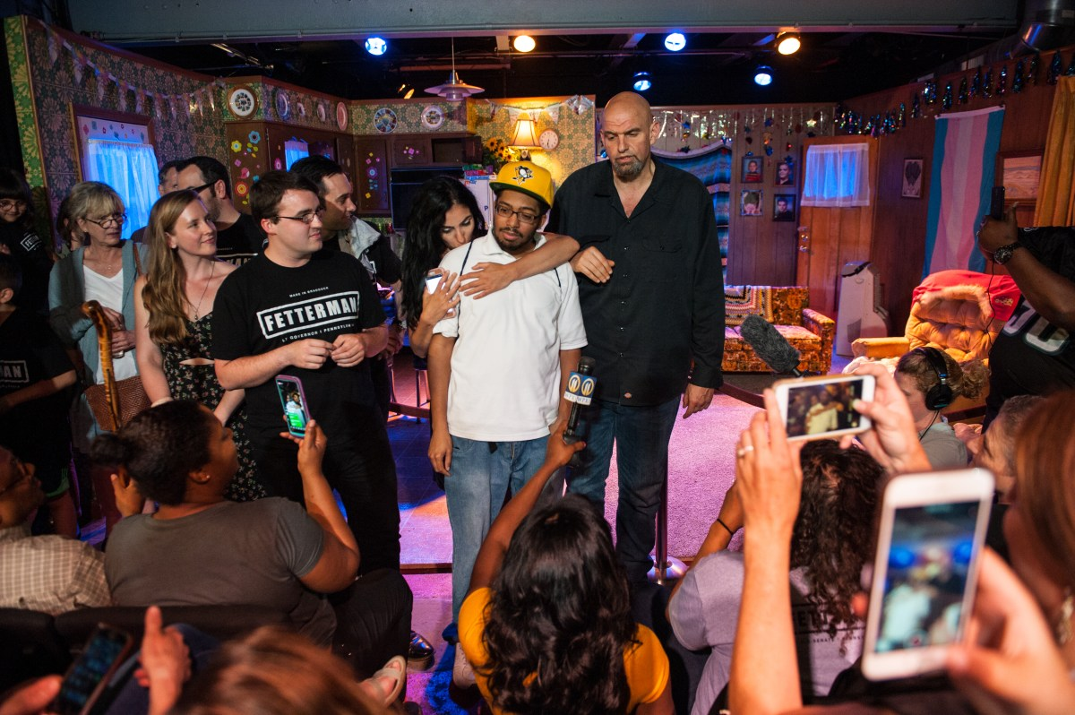 "Mayor of Braddock and projected Democratic nominee for lieutenant governor of Pennsylvania John Fetterman, right, addresses his supporters at his primary election watch party as his wife, Gisele, hugs longtime friend and Fetterman supporter Jovan Villars, 36, of Swissvale on Tuesday, May 15, 2018, at Barebones Black Box Theater in Braddock. ""He's an advocate for a lot of people that can't be seen,"" said Villars, who met Mr. Fetterman 17 years ago when Villars was enrolled in a job training program through Hill House and Americorps that Mr. Fetterman was working for. ""Him being up here was just like me being up here."" (Stephanie Strasburg/Post-Gazette)"