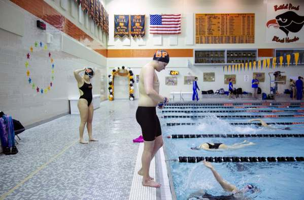 "Colby Love, center, 18, of Bethel Park, looks down toward the water as he steps to the edge of the pool for warm-ups on senior night before the swim team's meet against Canon-McMillan, Thursday, Feb. 7, 2019, at Bethel Park High School in Bethel Park. ""There were like, points where I like... I wasn't even able to look past like, tomorrow,"" says Love thinking back to the consuming depression and anxiety he battled in his sophomore and junior years of high school. Love, a swimmer since childhood, was a rising star on the Bethel Park High School girls swim team, until sudden and severe mental health issues began to surface. After taking a year off of both school and swimming, undergoing bouts of treatment and therapy, Love decided to have top surgery. This is when he officially changed his gender to male and began to find solace. Getting back in the pool, in what can be considered his senior year of high school, Love now swims not for the team, not for the times, not for the coaches, but for himself."