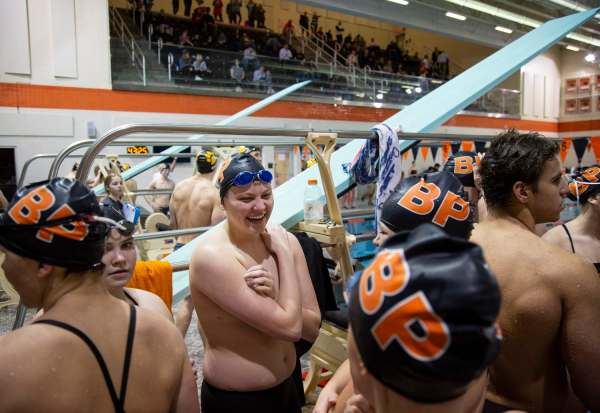 "Colby Love, center, 18, of Bethel Park laughs as he talks with fellow Bethel Park swimmers before competing in the boys freestyle relay, Tuesday Jan. 29, 2019, at Bethel Park High School in Bethel Park. For the past two years, Love has battled with severe depression and anxiety along with an overwhelming feeling that he wasn't meant to be a girl. After taking a year off from both swimming and school in his junior year, Love received treatment for his declining mental health. In this year, he also decided to have top surgery before returning to the pool for his senior year. ""I knew going back into swimming, after the year off or whatever, that I like went into it saying like, I'm doing this for me and not anyone else. And um, that I was like, I can't compare the person that I was the last time I swam, to the person that I am now."""
