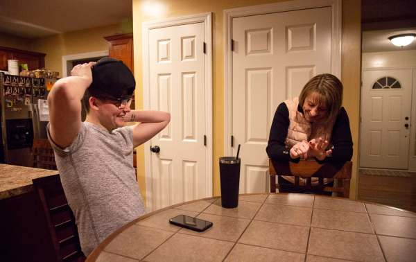 "Colby Love, 18, of Bethel Park, left, adjusts his hat while talking with his mom, Kim Love of Bethel Park, about swim bags given out at his swim team's end of the year banquet Monday Feb. 18, 2019, at his home in Bethel Park. Love describes his relationship with his mom as being very close. ""She's kid of like my best friend, I tell her anything. We do a lot of stuff together,"" expains Colby."