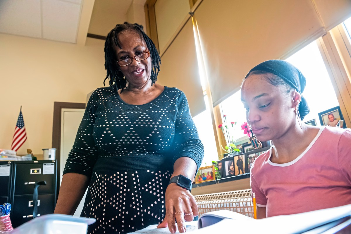 Mrs. Sharon Brentley of the North Side, left, checks the work of Destiny Jenkins of the North Side, right, during her tenth grade World History class, Friday, Feb. 15, 2019, at Perry Traditional Academy in the North Side. Mrs. Sharon Brentley was part of Pittsburgh Perry High SchoolÕs Class of 1977 who were the first students to attend the Northside school all four years after it formally integrated in 1973. She went back to Perry to teach and has been there for 15 years. (Michael M. Santiago/Post-Gazette)