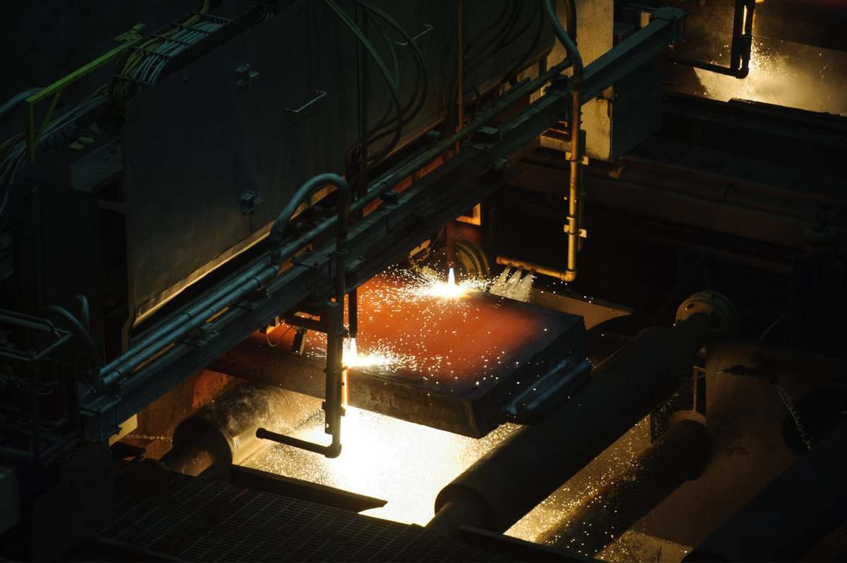 Sparks fly against steel slabs.