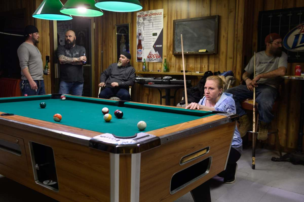 "Laborer April VanHorn, right, 40, of Mingo Junction, Ohio, shoots pool in a pool league, Thursday, Feb. 28, 2019, at Spuds Parkview Inn in Mingo Junction, Ohio. ""Everybody's hopeful,"" said VanHorn of JSW Steel restarting the mill in town. Her father worked in the mill before it closed, and she is applying to work there as a laborer as well."