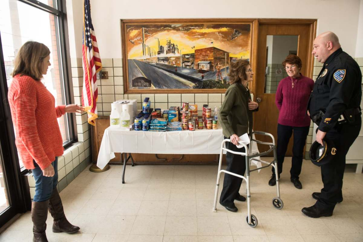 From left to right, volunteer Kristen Wheeler-Kurner, 38, Sophie Schoolcraft, 89, Mingo Junction treasurer, volunteer Kathleen Brockway, 73, and Police Chief Joseph Sagun, 47, talk in front of a table of donated food in early March in the Mingo Junction municipal building. In the background is a painting of the town that depicts the steel mill looming large. Schoolcraft organizes food drives and the pick-up and purchase of food and clothing for struggling residents.