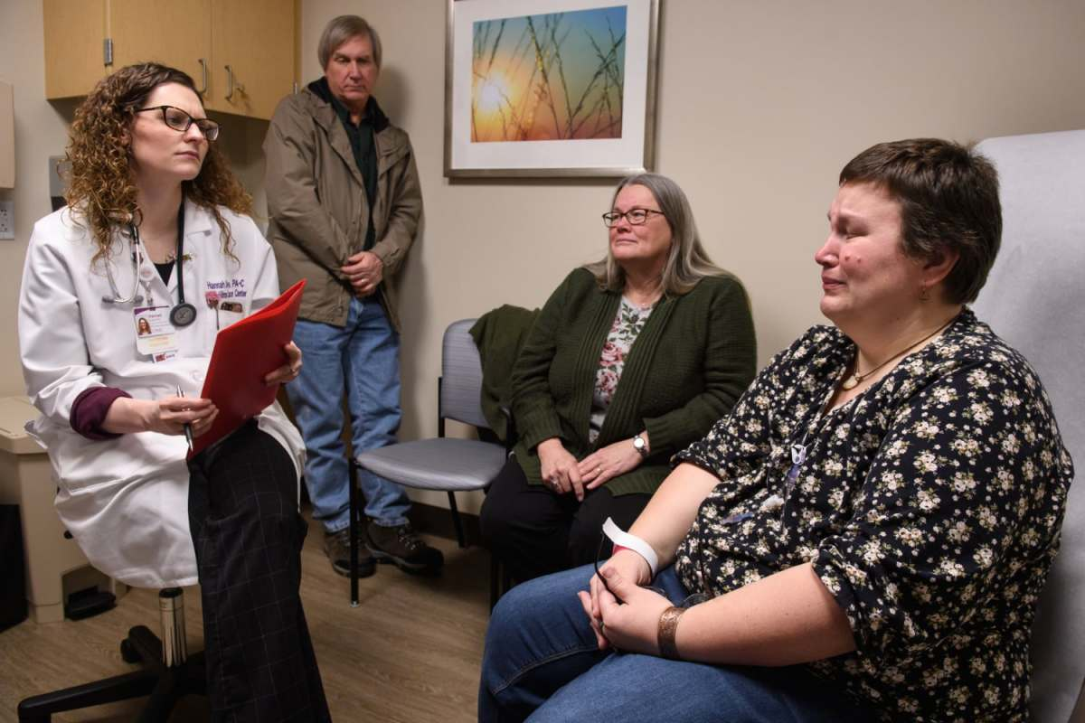 Physician Assistant Hannah Doyle, left, reacts as she listens to Mary Beth Brown, right, 37, talk about her emotional struggles as a mother, wife, and daughter while undergoing treatment for her stage four, metastatic breast cancer during a visit to the UPMC Hillman Cancer Center, Wednesday, Jan. 9, 2019, in Shadyside. Ms. Brown's parents, Douglas Basinger and Mary Lou Basinger, both 63, at back, often drive their daughter to the city for medical appointments and treatment. Mrs. Basinger quit her job in order to help babysit Ms. Brown's children and take care of the Browns' home.