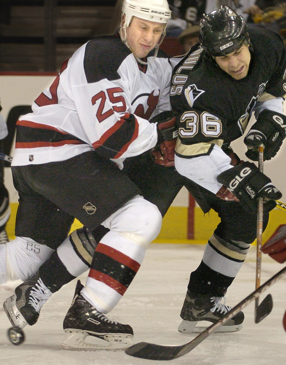 Tom Kostopoulos fights for the puck with New Jersey defenseman David Hale at Mellon Arena on Jan. 20, 2004. (Peter Diana/Post-Gazette)