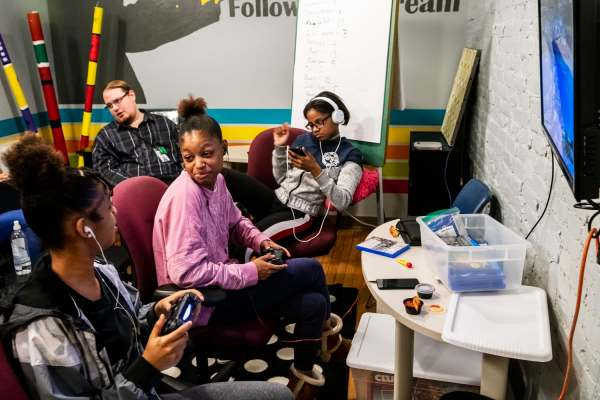 Sisters from left, Diana Washington and De'aija Washington share a moment while playing video games as Danielle Washington listens to music on her phone during the Volunteers of America's Teens with a Purpose program, Thursday, Jan. 24, 2019, at Transitional Housing Program & Emergency Family Shelter in Louisville, Ky.