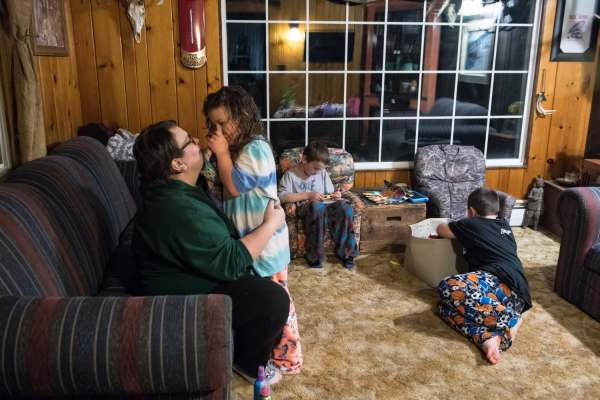 Mary Beth Brown, left, 37, gives her daughter Nellie, 6, a hug goodnight as her sons Oliver, center, 7, and Anthony, right, 8, play before bed, Wednesday, April 3, 2019, at the Brown family farm straddling Saltlick and Bullskin. Pain and exhaustion from Mary Beth's breast cancer prevents her from walking upstairs to tuck the children into bed, a ritual her husband has taken over.