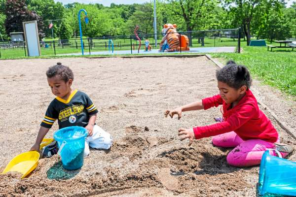 Ezirah Reyes, 3, of East Pittsburgh, left,  and his sister Zanerra Reyes, 5, of East Pittsburgh, play in the sand during a family outing with McKeesport Family Center, Friday, May 31, 2019, at Renziehausen Park in McKeesport. McKeesport Family Center helps families with young children and their parents with free services -- everything from parenting advice and classes that promote healthy child development to helping with day-to-day needs. (Michael M. Santiago/Post-Gazette)