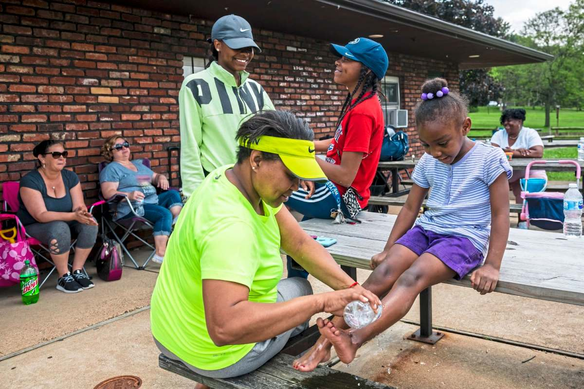 Yolanda Wade, of McKeesport, left, washes the feet of Savanna Wiggins, 5, of McKeesport, right, during a family outing with McKeesport Family Center, Friday, May 31, 2019, at Renziehausen Park in McKeesport. (Michael M. Santiago/Post-Gazette)