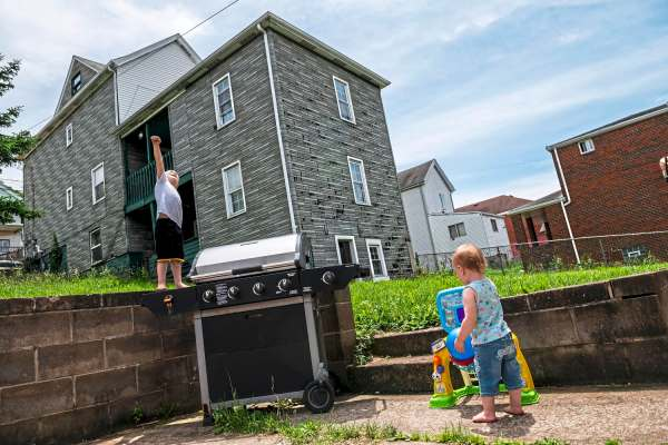 Jaxen Jakub, 5, of Glassport, raises his fist as he imitates Superman as his sister Karlee Brydges, 1, of Glassport, plays with a toy basketball hoop in the backyard of their new home, Saturday, June 8, 2019, in Glassport. (Michael M. Santiago/Post-Gazette)