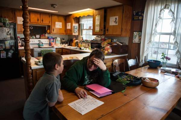 Oliver Brown, left, 7, protests as he does homework with his mother, Mary Beth Brown, 37, at their kitchen table, Wednesday, April 3, 2019, at their family farm straddling Saltlick and Bullskin. Oliver was born prematurely by C-section and needed extra help in school, so the Browns sent him to a private Christian school that could accommodate his developmental disability without a specific diagnosis. The school community raised money so the other Brown children could also attend the school.