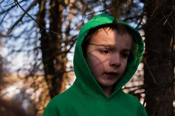 "Shadows fall against the face of Oliver Brown, 7, as he plays hide-and-seek with his siblings, Wednesday, April 3, 2019, at their family farm straddling Saltlick and Bullskin. Oliver ""does not like change,"" his mother Mary Beth explains, which makes it even harder to explain what's happening when she is gone for days at a time for cancer treatment. ""It's hard for them to understand what 'stage four' means,"" she says."