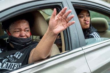 Debbie Johnson, left, and her daughter Alex Johnson, both of Monroeville, wave and kiss toward the window of their friend Gwendolyn Huddle, 86, (not pictured) during a May Day parade, Friday, May 1, 2020, at Independence Court of Monroeville. Many of the residents had not seen their loved ones in months. (Steph Chambers/Post-Gazette)