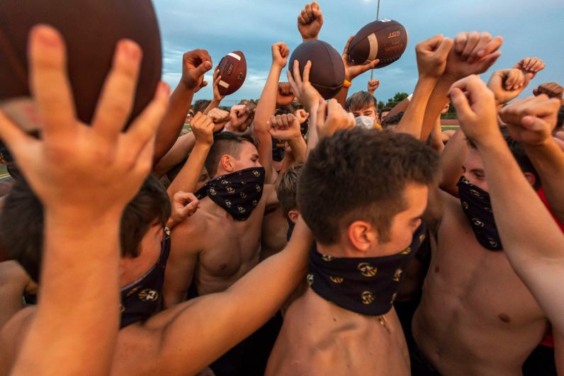 Evening sunlight is cast on masked Thomas Jefferson football players as they gather for a break down after practice, Wednesday, July 22, 2020, at the school's stadium in Jefferson Hills. (Steph Chambers/Post-Gazette)
