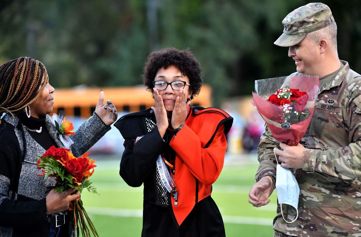 Beaver Falls drum major Candice Jones, center, reacts as her father, Col. Loren Duwel, right, surprises her next to her mother, Mary Harris-Jones, during senior night before her team takes on New Brighton, Friday, Oct 2, 2020, at Geneva College in Beaver Falls. Jones, originally deployed to Afghanistan, contracted COVID-19 and has been recovering at Walter Reed Medical Center in Bethesda, Md. He was able to leave the facility for a day to see his daughter, whom she hasn't seen in months. (Matt Freed/Post-Gazette)